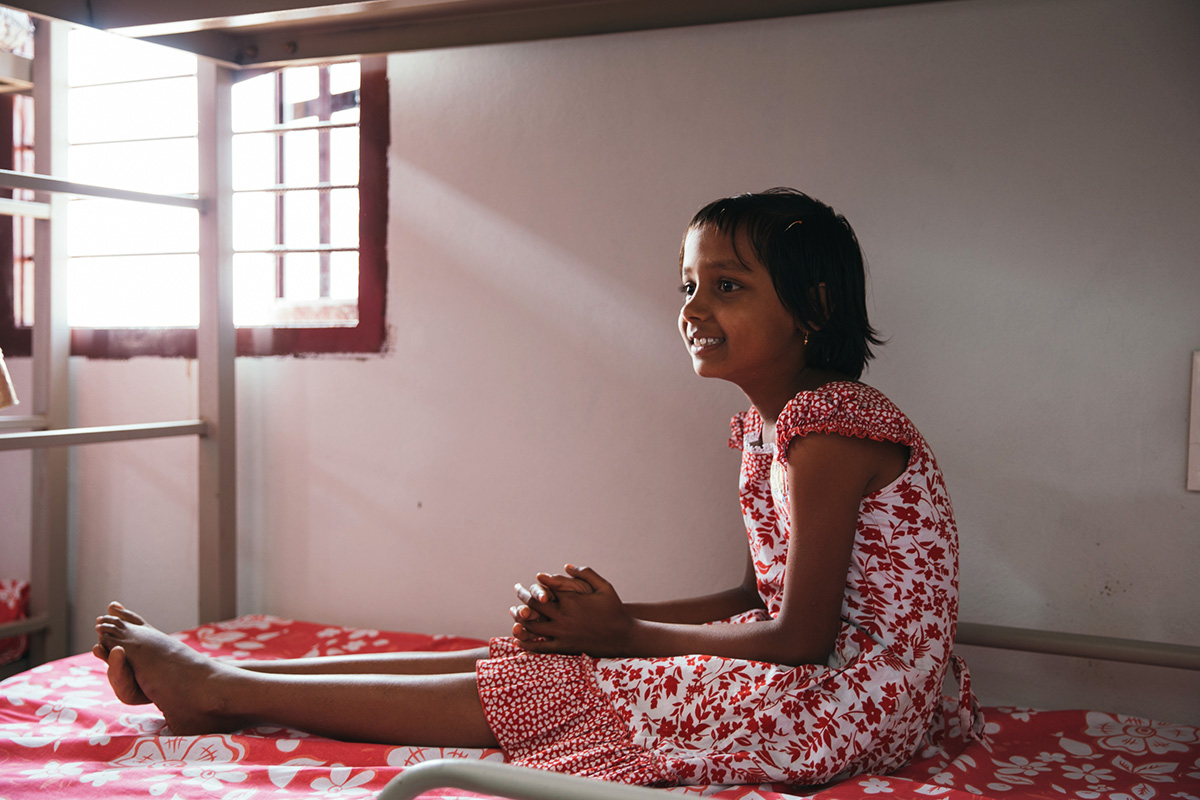 Indian girl sitting on her bed